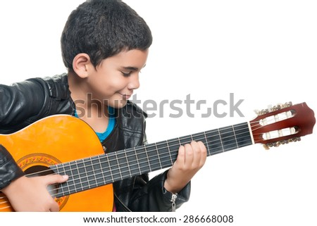 Cute hispanic boy playing an acoustic guitar isolated on a white background - stock photo