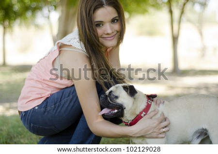 Cute hispanic brunette and her pug dog having fun at the park