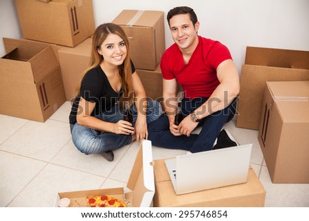Cute Hispanic couple enjoying their first day in their new home while eating pizza and watching a show in a laptop computer - stock photo