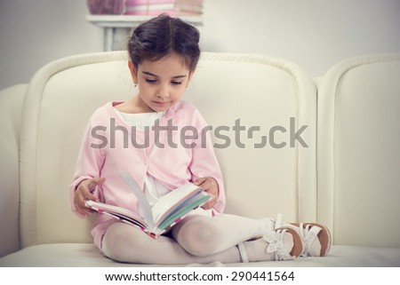 Cute hispanic little girl reading book on couch at home - stock photo