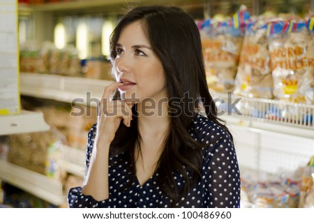 Cute hispanic woman trying to decide what to buy - stock photo