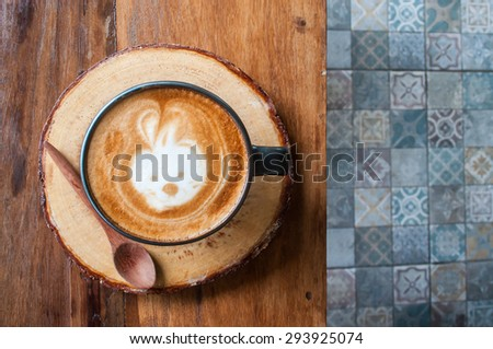 Cute Hot Latte Coffee on the wooden table over ceramic tile floor - stock photo