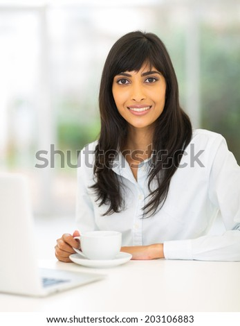 cute indian businesswoman drinking coffee in office