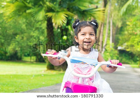 Cute Indian girl biking at outdoor garden. Child having fun with bicycle. - stock photo