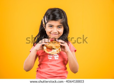 cute indian girl eating burger, small asian girl and burger, isolated over yellow background
