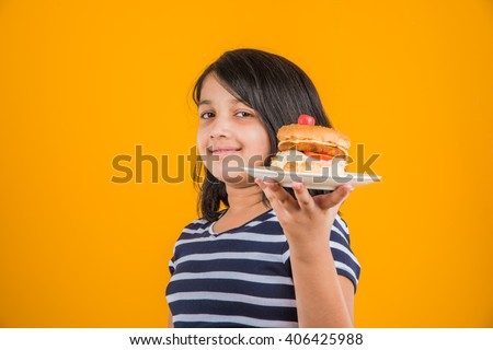 cute indian girl eating burger, small asian girl and burger, isolated over yellow background - stock photo