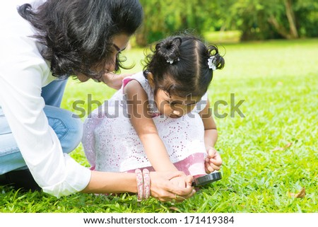 Cute Indian girl peeking through magnifying glass with parent on green lawn. Mother and daughter exploring nature at outdoor garden. - stock photo