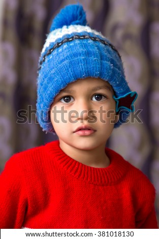 Cute Indian Kid striking a pose wearing red sweater and blue cap with a cute smile  - stock photo