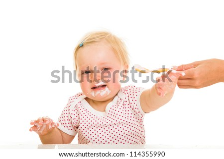 Cute infant girl learining to eat with spoon