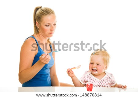Cute infant girl learining to eat with spoon - stock photo