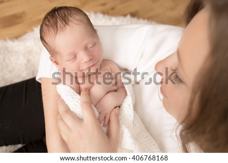Cute infant on the hands of mother - stock photo