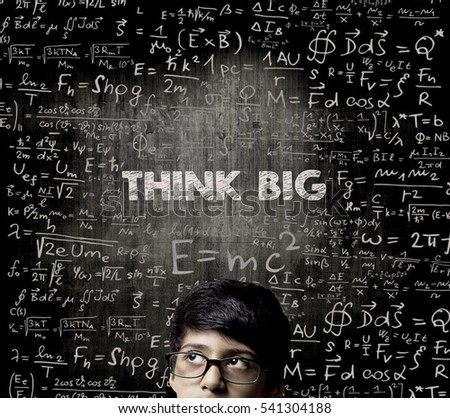 Cute Intelligent Little Boy Looking Up Thinking and Wearing Glasses Standing Before A Chalkboard, Chemical Formulas Are Written On Board With The Chalkboard Typography Of The Words THINK BIG