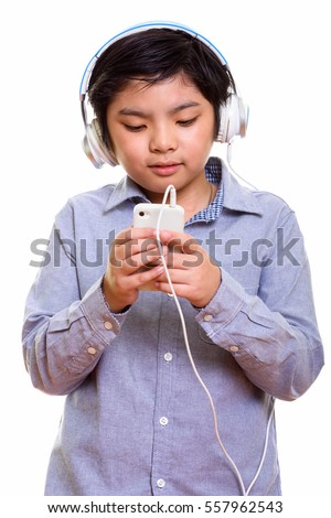 Cute Japanese boy listening to music while using mobile phone isolated against white background