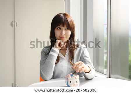 Cute Japanese business woman saving money