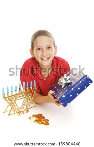 Cute Jewish boy with his Chanukah menorah, gift, and a dreidel and chocolate gelt coins.  White background.   - stock photo