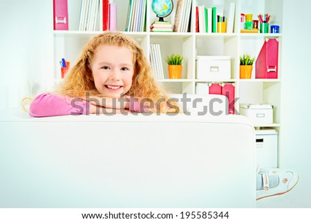 Cute joyful girl sitting on a sofa at home. - stock photo