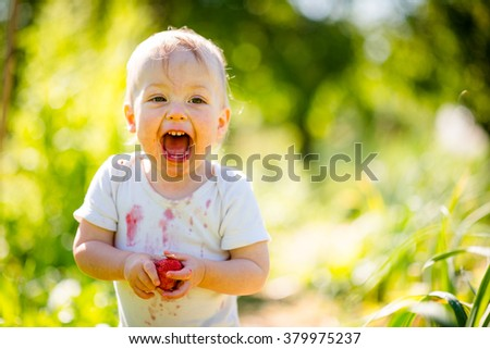 Cute joyous child with strawberry - outdoor in backyard garden on sunny day
