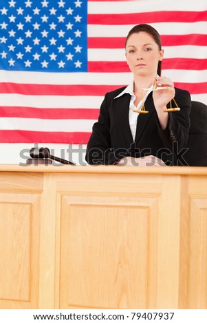 Cute judge holding scales of justice with an American flag in the background - stock photo