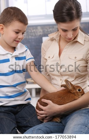 Cute kid and mum stroking pet bunny at home. - stock photo