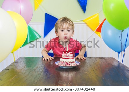 Cute kid blowing out a birthday candle - stock photo