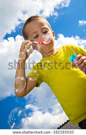 Cute kid blowing soap bubbles - stock photo
