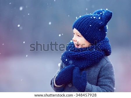 cute kid, boy in winter clothes playing under the snow