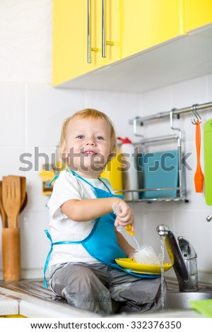 Cute kid boy washing dishes and having fun in the kitchen - stock photo