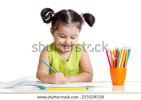 Cute kid drawing with colorful pencils and smiling, isolated on white - stock photo