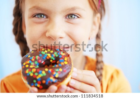 Cute kid girl eating sweet donuts - stock photo