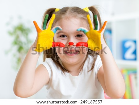 cute kid girl have fun painting her hands and face