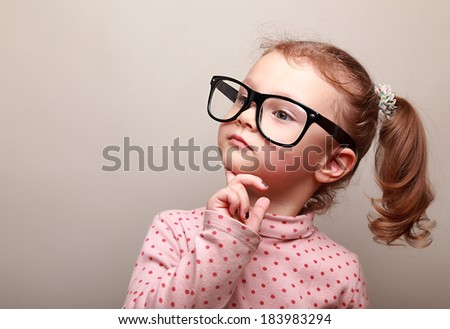 Cute kid girl in glasses thinking and looking serious - stock photo
