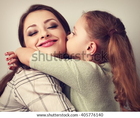 Cute kid girl kissing and cuddling her enjoying beautiful mother in studio. Toned closeup portrait of family love.