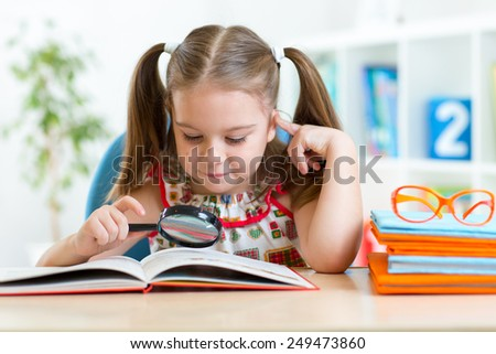cute kid girl looks through a magnifying glass with book sitting at table - stock photo