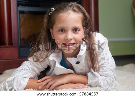 Cute kid girl lying on white carpet and looking at camera