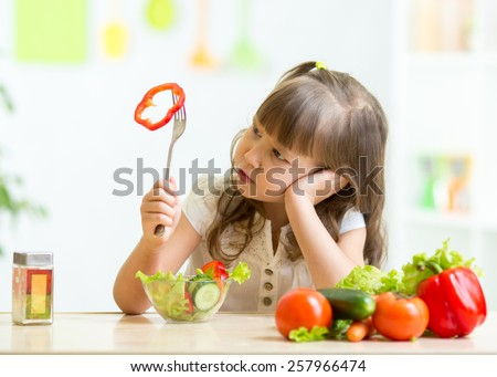 Cute kid girl not wanting to eat healthy food at kitchen - stock photo