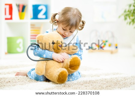 Cute kid girl playing doctor with plush toy at home - stock photo