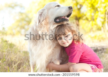 Cute kid girl playing with dog outdoors. Portrait of blonde little girl holding pet - stock photo