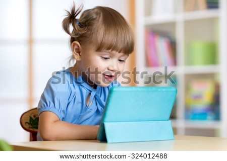 cute kid girl playing with tablet computer at home