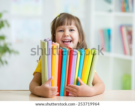 Cute kid girl preschooler with books at home - stock photo