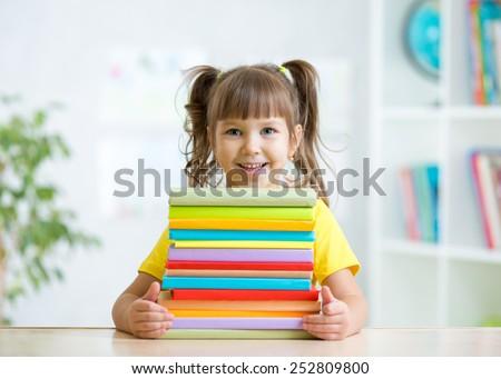 Cute kid girl preschooler with books indoor - stock photo