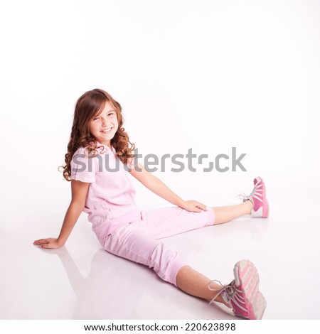 Cute kid girl wearing sporty clothes. Portrait of little girl posing on white