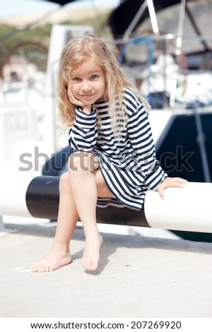 Cute kid girl wearing striped dress outdoors - stock photo