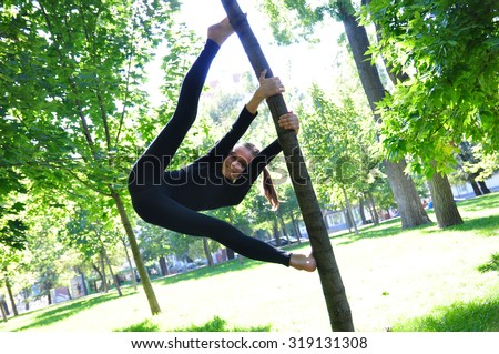 Cute kid having fun outdoor workout uses a tree as a gymnastic pole.  - stock photo