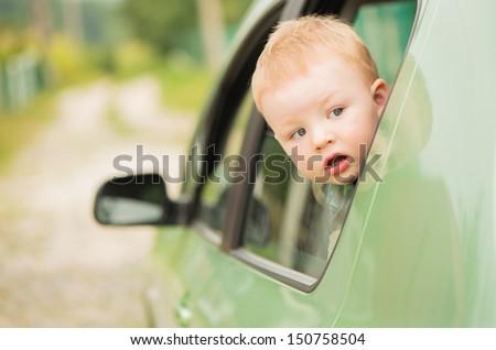 cute kid head outside green auto window - stock photo