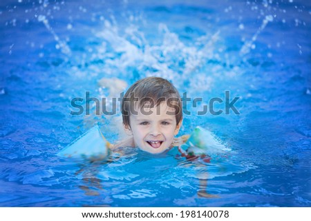 Cute kid in a big swimming pool - stock photo