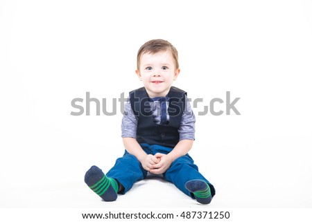 Cute kid in a striped knitted socks, blue jeans and a batch file with a vest sits isolated on a white background