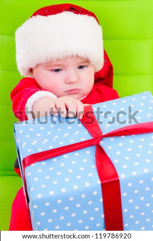 cute kid in Santa Claus clothes. sitting on a green chair and holding a big gift box - stock photo