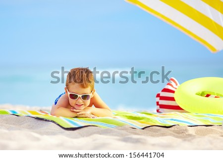cute kid in sunglasses resting on colorful beach - stock photo