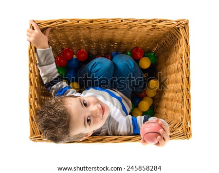 Cute kid inside basket playing with colored balls - stock photo
