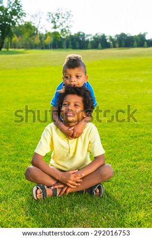 Cute kid is hugging his older brother on the sunny glade.